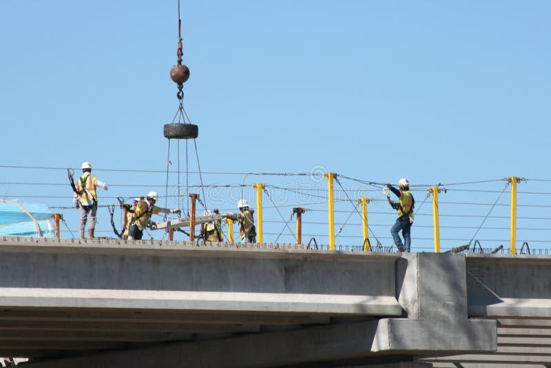 Ομαδική εργασία: Στο διακρατικό 69 εργοτάξιο οικοδομής, εργασία Laborers από κοινού στοκ φωτογραφίες