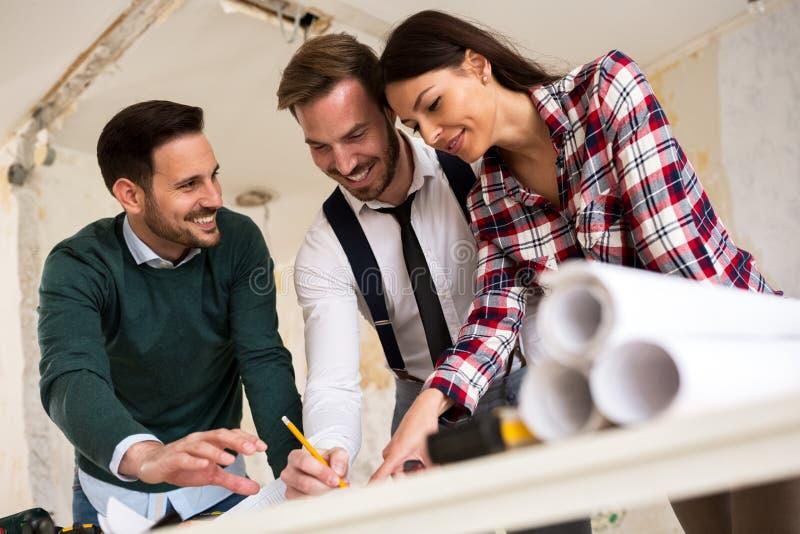 Ομαδική εργασία Τρεις νέοι αρχιτέκτονες που εργάζονται σε ένα πρόγραμμα στοκ εικόνα