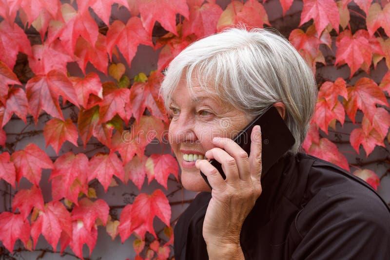 Ομιλία γυναικών χαμόγελου η ευτυχής ηλικιωμένη έξω σε ένα κινητό τηλέφωνο με το συμπαθητικό φθινόπωρο φεύγει στοκ φωτογραφίες με δικαίωμα ελεύθερης χρήσης