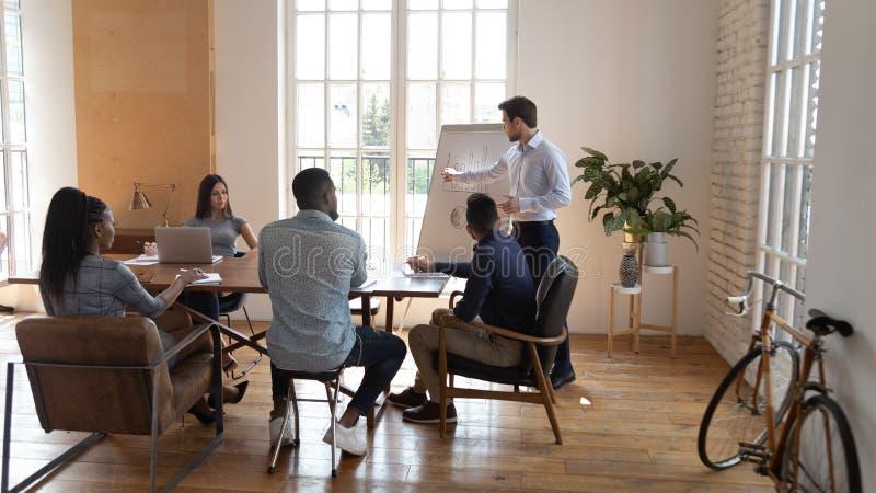 Ομιλητής επιχειρηματιών που παρουσιάζει στους πολυφυλετικούς επιχειρηματίες στην αρχή στοκ εικόνες