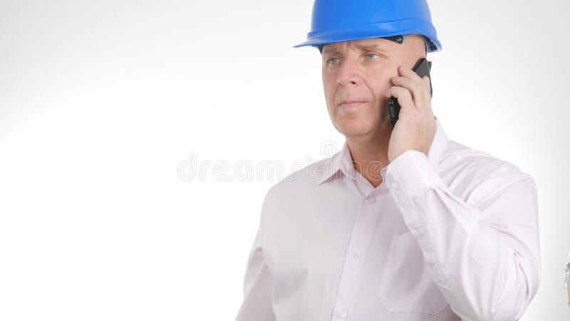 Ομιλούσα επιχείρηση εικόνας μηχανικών που χρησιμοποιεί το κινητό τηλέφωνο στοκ φωτογραφίες