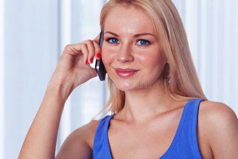 ομιλούσες νεολαίες γυναικείων κινητές τηλεφώνων στοκ εικόνες