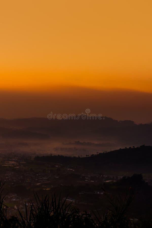 Ομιχλώδες χωριό και βαλμένο σε στρώσεις βουνό στην ανατολή στοκ φωτογραφία