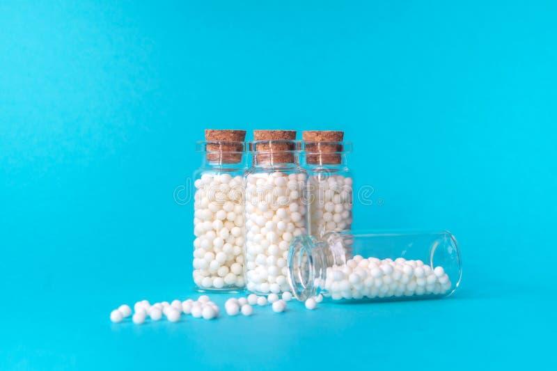 Ομοιοπαθητικά globules σε τέσσερα μπουκάλια γυαλιού στο μπλε υπόβαθρο Globules είναι διεσπαρμένα από ένα μπουκάλι _ στοκ εικόνα