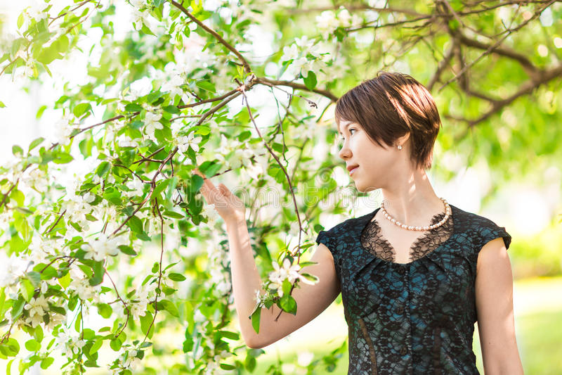 Ομορφιά, άνθρωποι, έννοια καλοκαιριού και άνοιξης - όμορφη νέα γυναίκα πέρα από το πράσινο ανθίζοντας υπόβαθρο κήπων στοκ φωτογραφία