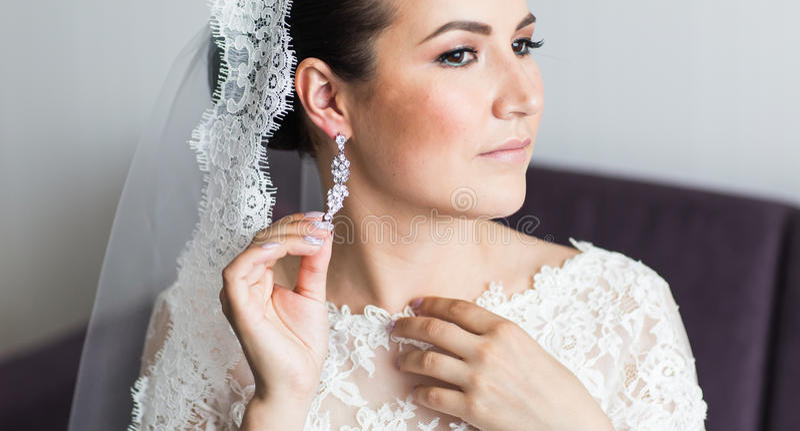 Ομορφιά και έννοια κοσμημάτων - γυναίκα που φορά τα λαμπρά σκουλαρίκια διαμαντιών στοκ εικόνα