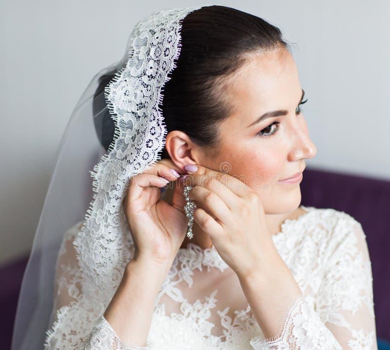 Ομορφιά και έννοια κοσμημάτων - γυναίκα που φορά τα λαμπρά σκουλαρίκια διαμαντιών στοκ εικόνα με δικαίωμα ελεύθερης χρήσης