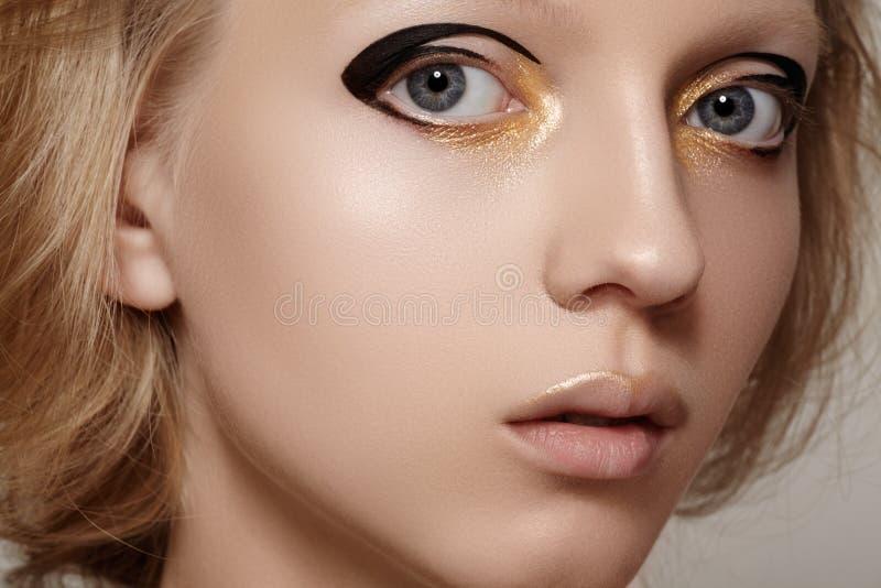 Ομορφιά & μόδα. Πρότυπο πρόσωπο κοριτσιών με τη φωτεινή σύνθεση σκαφών της γραμμής διακοπών χρυσή και μαύρη, καθαρό δέρμα στοκ φωτογραφία