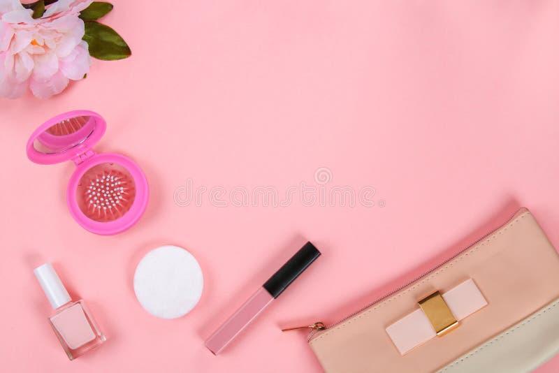 Ομορφιά που τίθεται με τα διακοσμητικά καλλυντικά στιλβωτική ουσία, βούρτσες και τσάντα καρφιών στο ρόδινο πρότυπο άποψης υποβάθρ στοκ εικόνες με δικαίωμα ελεύθερης χρήσης