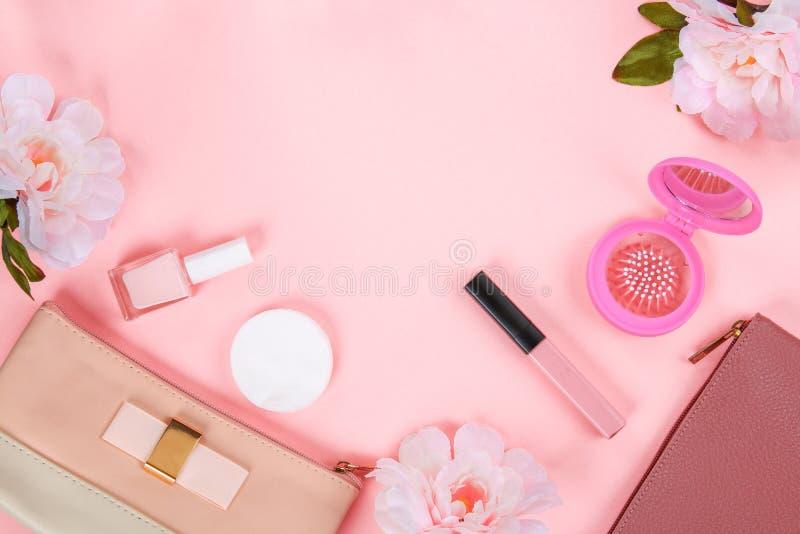 Ομορφιά που τίθεται με τα διακοσμητικά καλλυντικά στιλβωτική ουσία, βούρτσες και τσάντα καρφιών στο ρόδινο πρότυπο άποψης υποβάθρ στοκ εικόνες