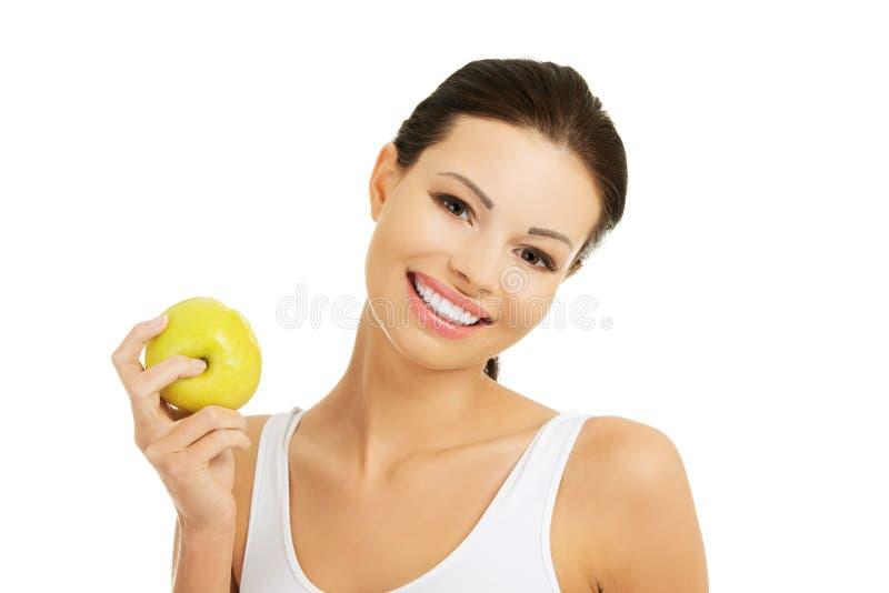 Ομορφιά χαμόγελου που κρατά το πράσινο μήλο στοκ φωτογραφίες