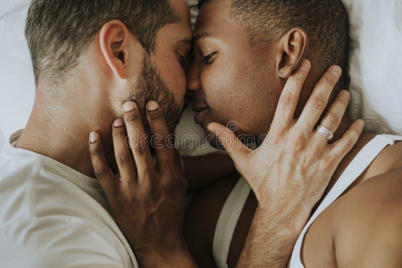 Ομοφυλοφιλική αγκαλιά ζευγών στο κρεβάτι στοκ εικόνες