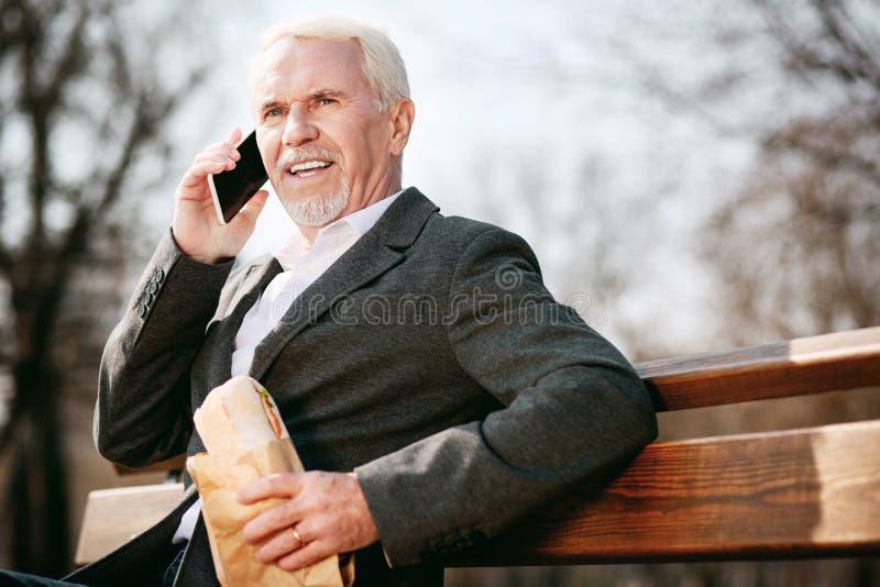 Ομοφυλοφιλικός ανώτερος επιχειρηματίας που τρώει το σάντουιτς στοκ φωτογραφίες