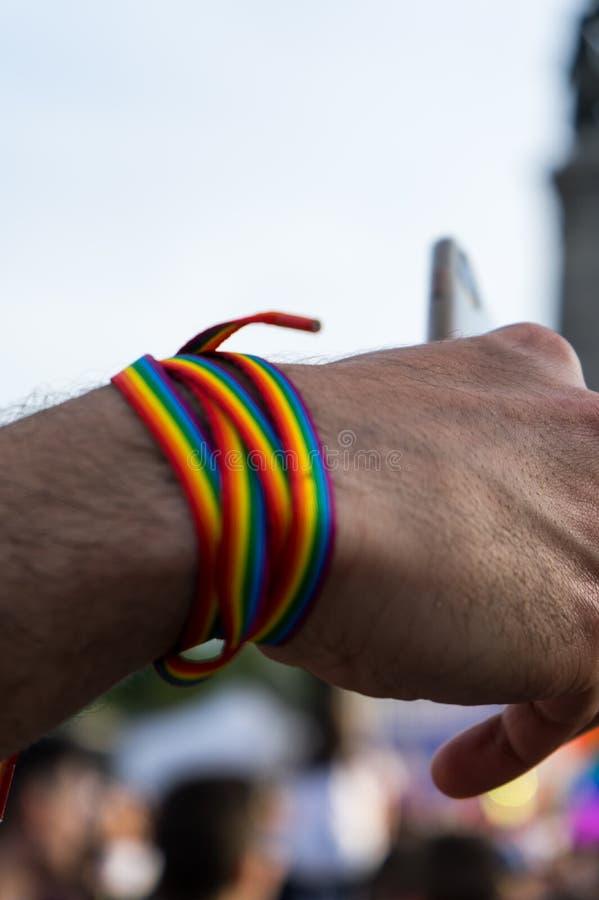 ομοφυλοφιλικός νεαρός άνδρας με το ουράνιο τόξο wristband, το βραχιόλι και το έξυπνο τηλέφωνο που παίρνουν selfie στο φεστιβάλ υπ στοκ εικόνα