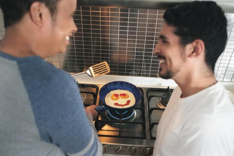Ομοφυλόφιλοι που τρώνε τα μαγειρεύοντας αυγά προγευμάτων στην εγχώρια κουζίνα στοκ εικόνες