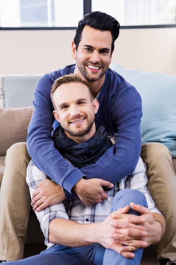 Ομοφυλοφιλικό ζεύγος που αγκαλιάζει στον καναπέ στοκ εικόνα με δικαίωμα ελεύθερης χρήσης