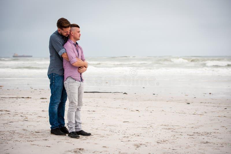 Ομοφυλόφιλοι που αγκαλιάζουν σε μια παραλία στοκ εικόνες