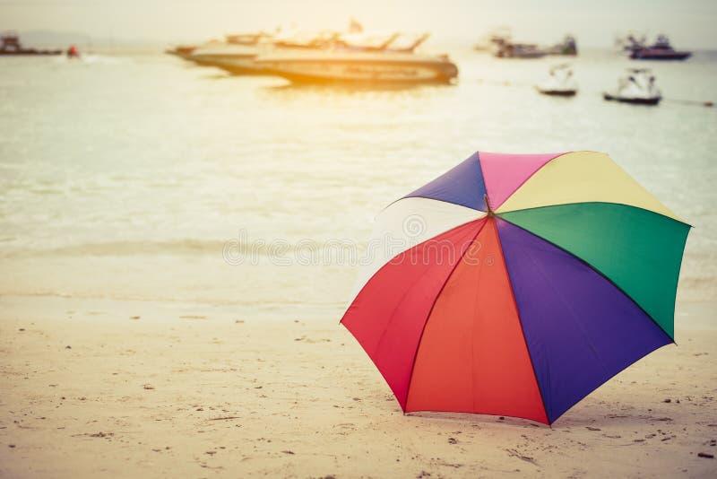 Ομπρέλα χρώματος ουράνιων τόξων στην παραλία Διακοπές και ξεχασμένο αντικείμενο ομο στοκ εικόνες