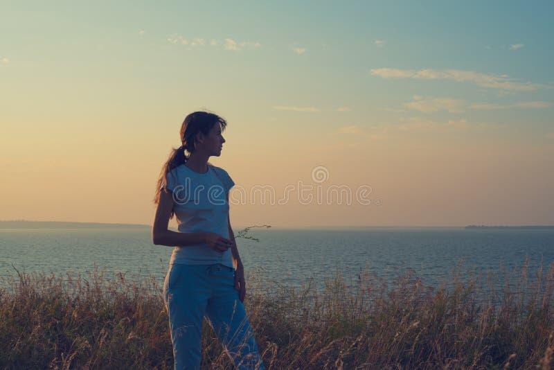 Ονειρεμένος γυναίκα, με τα άγρια λουλούδια στα χέρια της στοκ φωτογραφίες