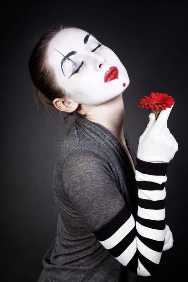 Ονειρεμένος γυναίκα mime με το κόκκινο λουλούδι στοκ εικόνες