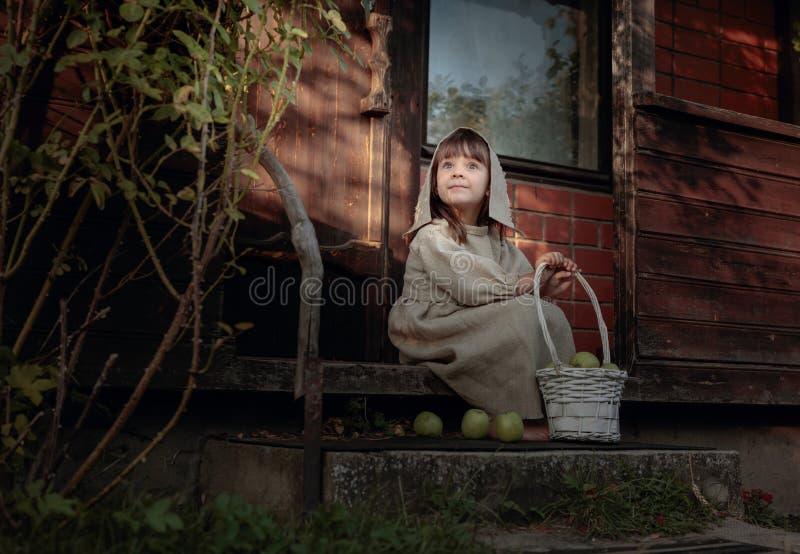 Ονειρεμένος κορίτσι με τα μήλα σε ένα θερινό βράδυ κοντά στο παλαιό σπίτι στοκ φωτογραφία με δικαίωμα ελεύθερης χρήσης