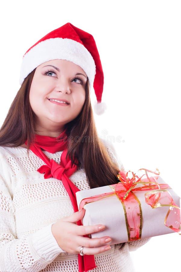 Ονειρεμένος κορίτσι με το καπέλο Χριστουγέννων και παρόν που ανατρέχει στοκ εικόνες