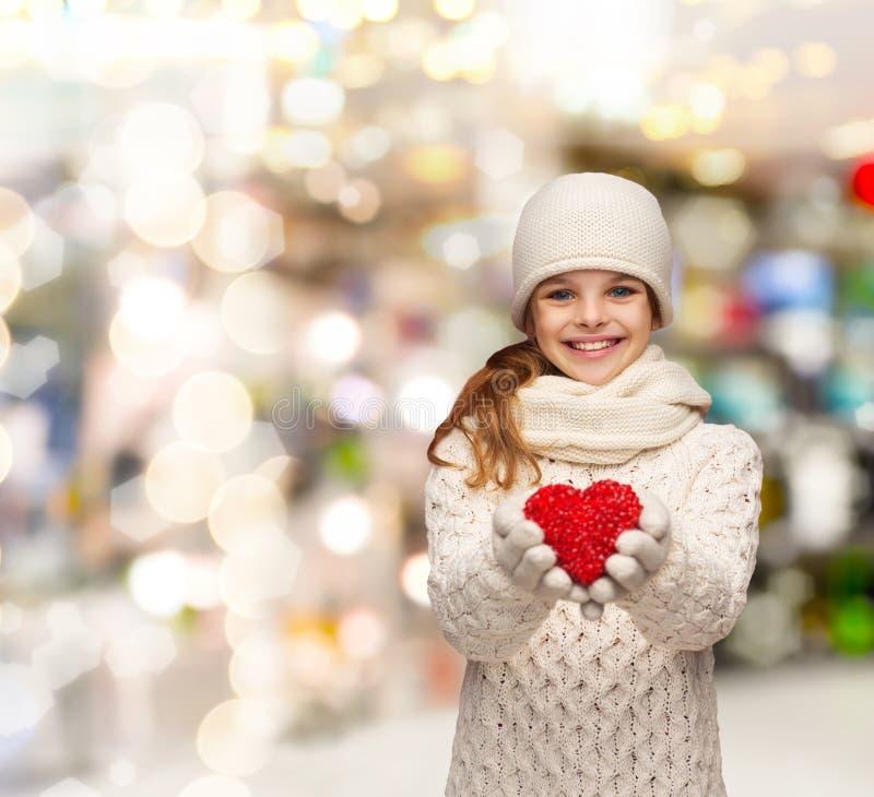 Ονειρεμένος κορίτσι στα χειμερινά ενδύματα με την κόκκινη καρδιά στοκ εικόνα