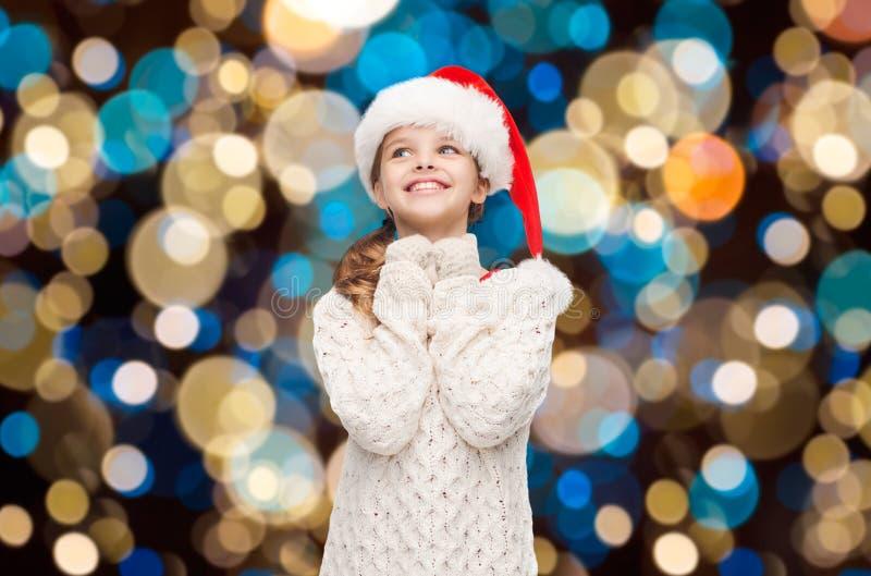 Ονειρεμένος κορίτσι στο καπέλο αρωγών santa πέρα από τα φω'τα στοκ φωτογραφία