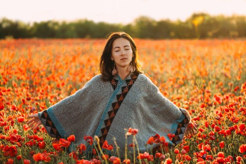 Ονειροπόλος όμορφη χαλάρωση γυναικών στο κόκκινο λιβάδι παπαρουνών στοκ εικόνες