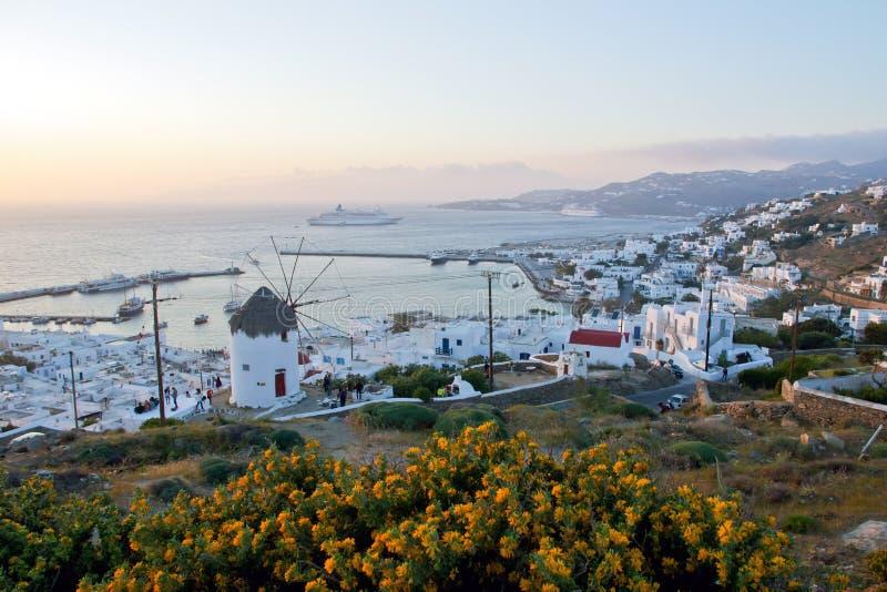 Ονειροπόλο ηλιοβασίλεμα πέρα από την πόλη της Μυκόνου και έναν παραδοσιακό ανεμόμυλο, Κυκλάδες, Ελλάδα στοκ εικόνα