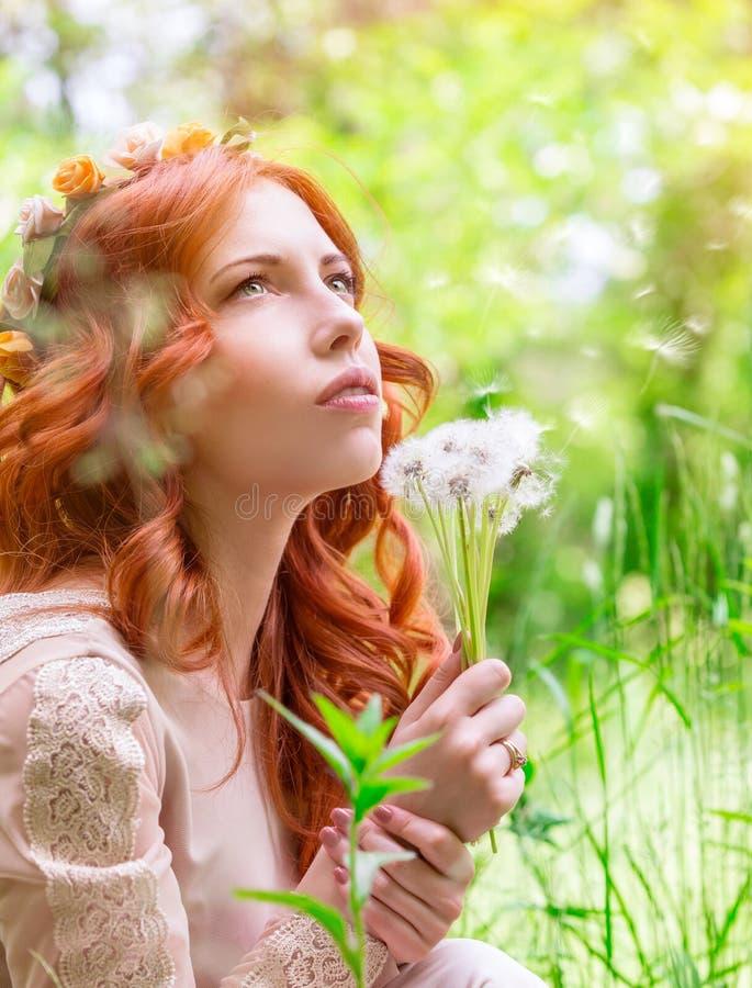 Ονειροπόλος γυναίκα με τις πικραλίδες στοκ εικόνες