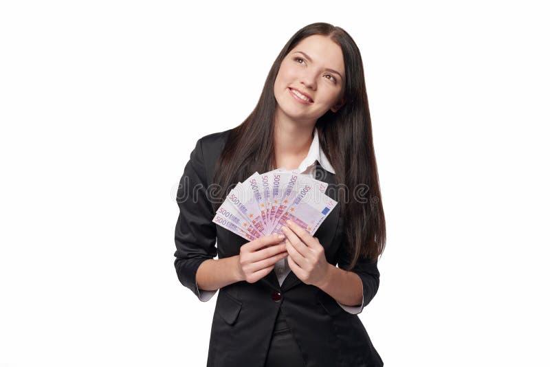Ονειροπόλος γυναίκα που κρατά τα ευρο- χρήματα στοκ εικόνα
