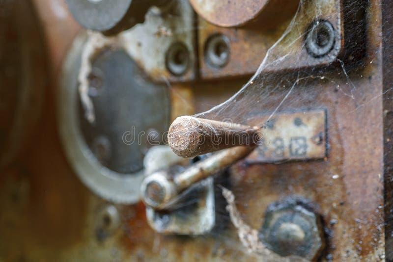 Οξυδωμένα στοιχεία ελέγχου της παλαιάς βιομηχανικής μηχανής που καλύπτεται με τον Ιστό αραχνών στοκ φωτογραφία