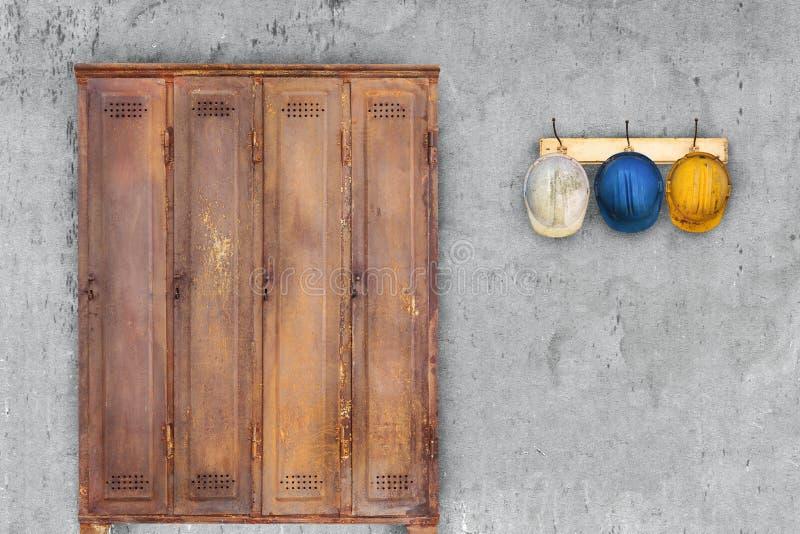 Οξυδωμένα τρύγος κράνη ντουλαπιών και κατασκευής που κρεμούν σε ένα καπέλο στοκ εικόνα