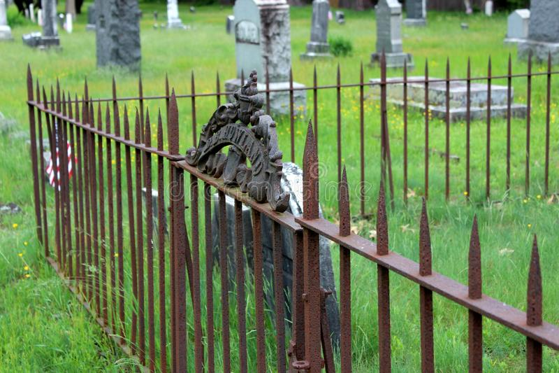 Οξυδωμένοι φράκτες που περιβάλλουν τις οικογενειακές ταφόπετρες με την πράσινη χλόη, νεκροταφείο Greenridge, Saratoga Springs, Νέ στοκ εικόνα