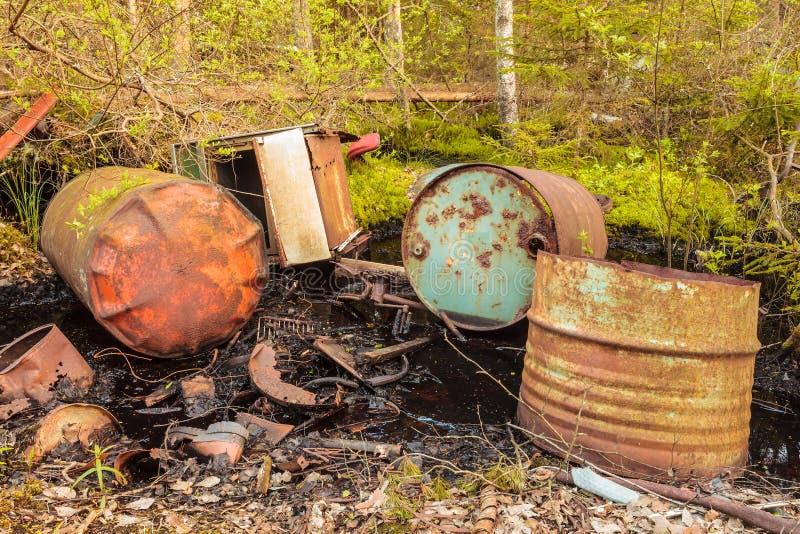 Οξυδωμένα βαρέλια αποβλήτων σε ένα δάσος στοκ εικόνες