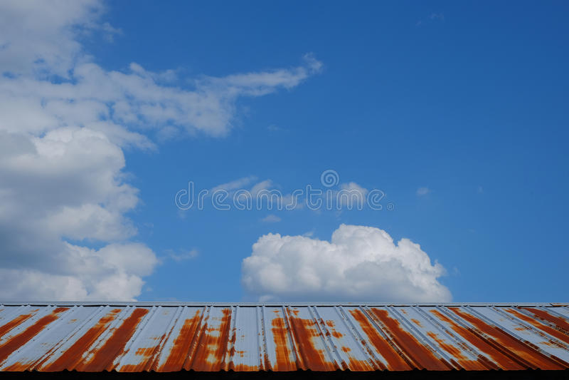 Οξυδώνοντας στέγη κασσίτερου μιας σιταποθήκης ενάντια σε έναν όμορφο μπλε ουρανό με το puf στοκ φωτογραφία με δικαίωμα ελεύθερης χρήσης