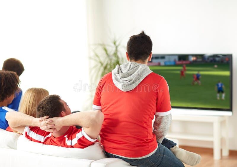 Οπαδοί ποδοσφαίρου που προσέχουν το παιχνίδι ποδοσφαίρου στη TV στο σπίτι στοκ εικόνα