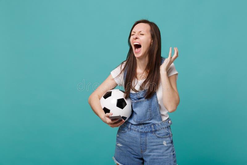 Οπαδός ποδοσφαίρου γυναικών κραυγής Displeased με τη σφαίρα ποδοσφαίρου που χρησιμοποιεί το κινητό τηλέφωνο, διαδίδοντας τα χέρια στοκ εικόνα