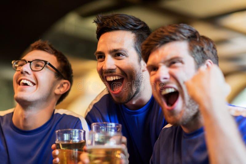 Οπαδοί ποδοσφαίρου ή φίλοι με την μπύρα στον αθλητικό φραγμό στοκ φωτογραφία