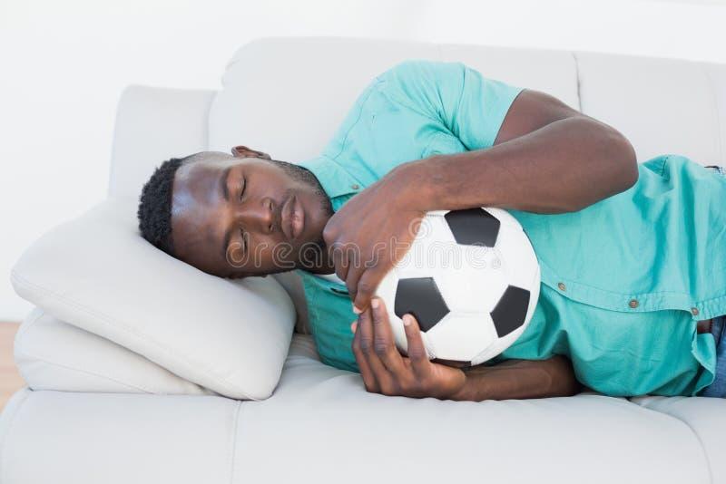 Οπαδός ποδοσφαίρου που αγκαλιάζει τη σφαίρα στον καναπέ στοκ εικόνες