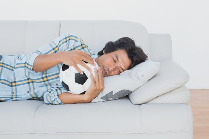 Οπαδός ποδοσφαίρου που αγκαλιάζει τη σφαίρα στον καναπέ στοκ φωτογραφία με δικαίωμα ελεύθερης χρήσης