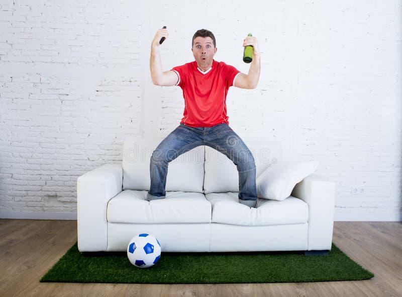 Οπαδός ποδοσφαίρου που προσέχει το στόχο εορτασμού ποδοσφαίρου TV στον καναπέ στον τάπητα χλόης που μιμείται την πίσσα σταδίων στοκ φωτογραφίες