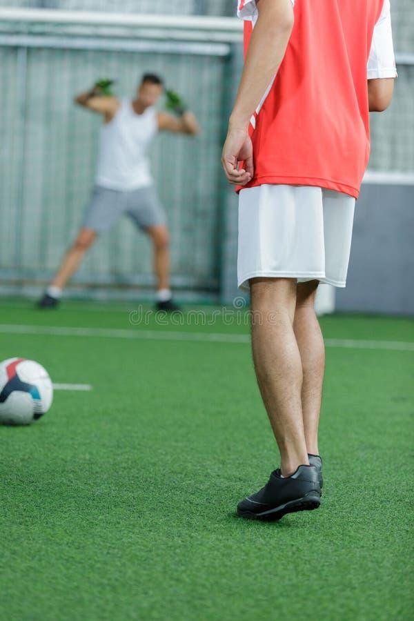 Οπισθοσκόποι νεαροί άνδρες που παίζουν το ποδόσφαιρο στο εσωτερικό στοκ εικόνα με δικαίωμα ελεύθερης χρήσης