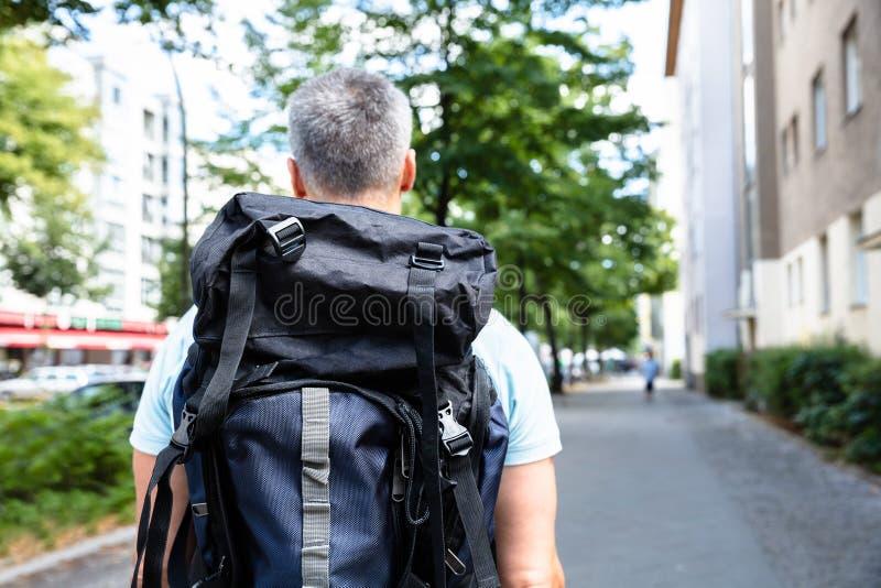 Οπισθοσκόπος ενός ατόμου που περπατά στο πεζοδρόμιο στοκ φωτογραφίες
