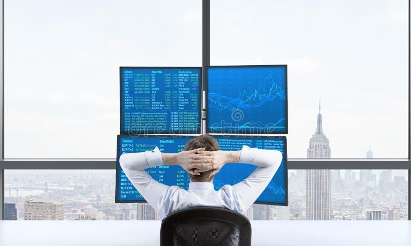 Οπισθοσκόπος ενός χαλαρώνοντας εμπόρου που κάθεται μπροστά από έναν σταθμό εμπορικών συναλλαγών που αποτελείται από τέσσερις οθόν στοκ φωτογραφίες με δικαίωμα ελεύθερης χρήσης