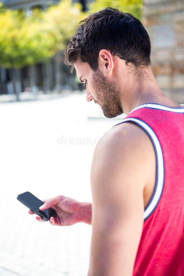 Οπισθοσκόπος ενός όμορφου αθλητή που στέλνει ένα κείμενο στοκ εικόνα με δικαίωμα ελεύθερης χρήσης