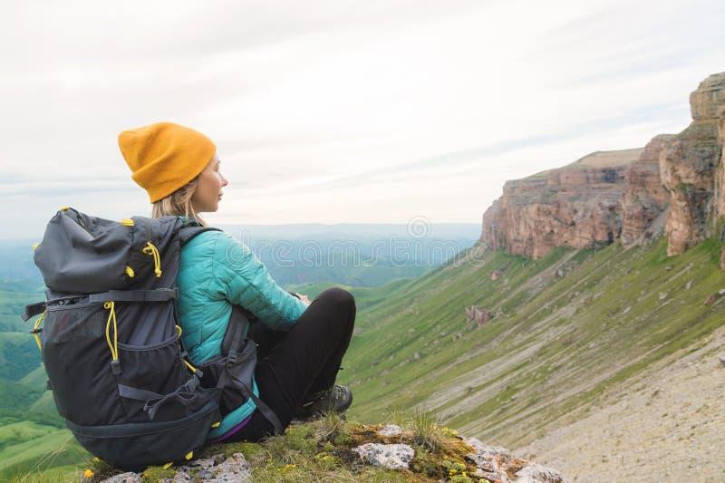 Οπισθοσκόπος μιας ελκυστικής θηλυκής συνεδρίασης τουριστών σε έναν χλοώδη λόφο που φορά τα γυαλιά ηλίου Απολαμβάνοντας θερινό ηλι στοκ φωτογραφία με δικαίωμα ελεύθερης χρήσης