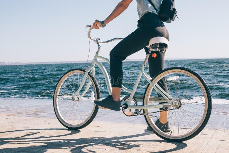 Οπισθοσκόπος νέα γυναίκα που σταματούν κατά τη διάρκεια ενός ποδηλάτου στοκ εικόνα