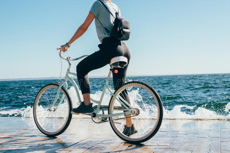 Οπισθοσκόπος νέα γυναίκα που σταματούν κατά τη διάρκεια του γύρου ποδηλάτων στοκ εικόνα